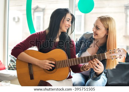 Girl teaching her friend to play guitar. - stock photo