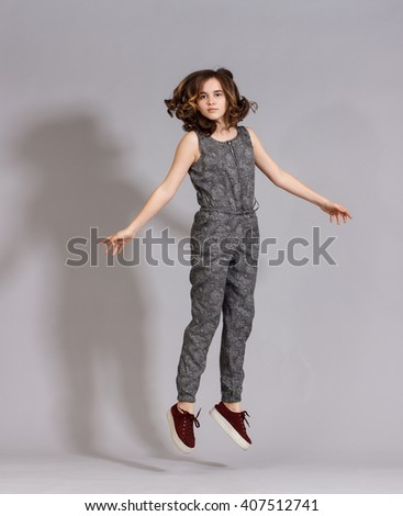Girl teenager in fashionable clothes have fun jumping on a black background . - stock photo