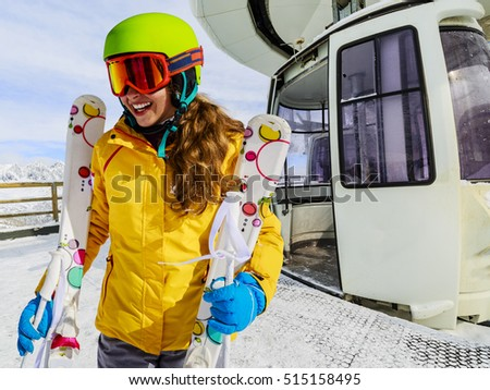 Girl teenager skier go out with ski on arms from the cable car in Italian Alps.