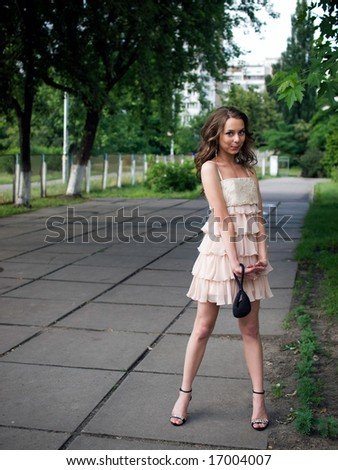Girl teenager stands outdoor against a trees background playfully.