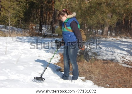 Girl teenager with metal detector in the forest at  early spring. Near Kiev,Ukraine - stock photo