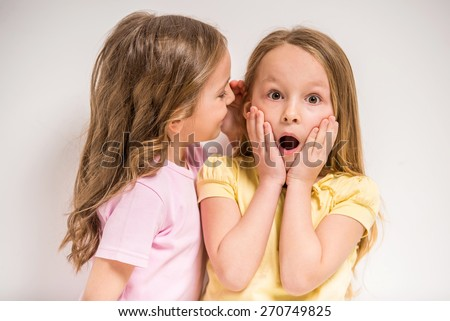 Girl telling a secret her friend on grey background. - stock photo