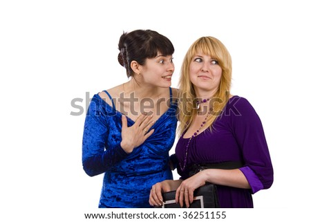 Girl telling a secret to another - gossip isolated over a white background. Woman friends series. Two happy women sharing funny gossip. Gossip - two beautiful girls in studio shot - stock photo