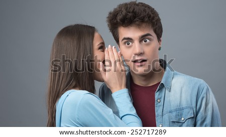 Girl telling secrets and gossips to his surprised friend - stock photo
