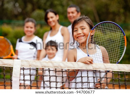 Girl tennis player with her family at the background - stock photo