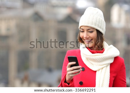 Girl texting in a mobile phone warmly clothed in the street in winter - stock photo