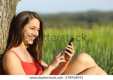 Girl texting in a smart phone relaxed in the country with a green field in the background - stock photo
