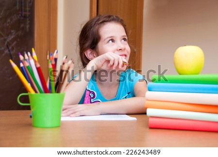 Girl thinking and writing on desk - stock photo