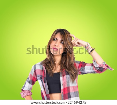 Girl thinking over isolated green background - stock photo