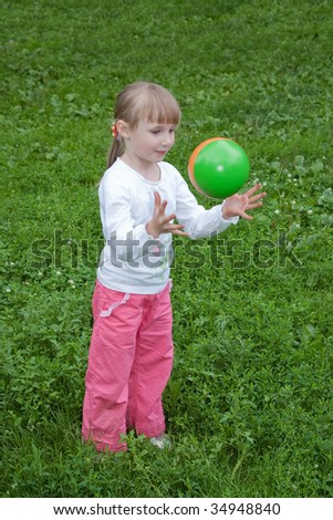 girl throwing a ball against a grass background
