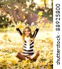 Girl throwing autumn leaves in air - stock photo