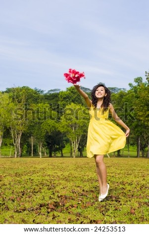 girl throwing flower towards the sky in an outdoor park