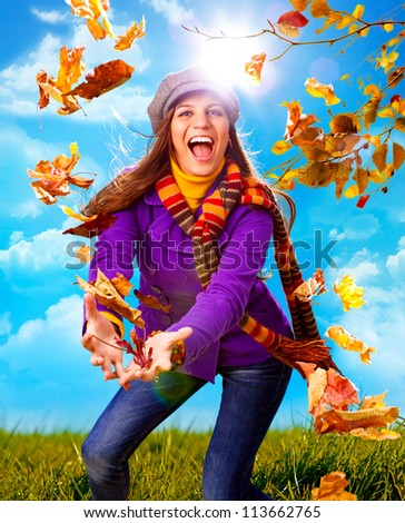 girl throwing leaves on an autumn-day - stock photo