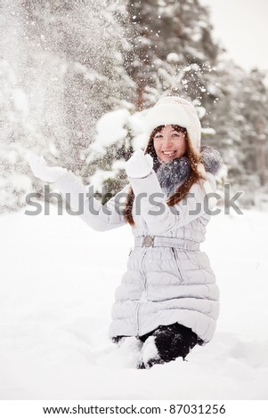 Girl throwing snow  in the air in park - stock photo