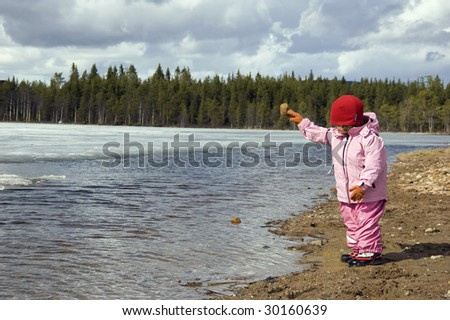 Girl throwing stones in the lake - stock photo
