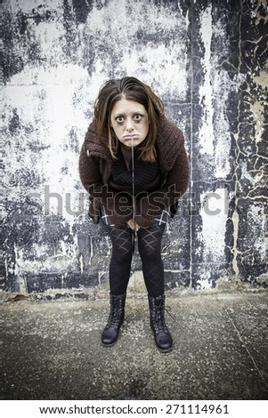 Girl throwing up sick in urban street - stock photo