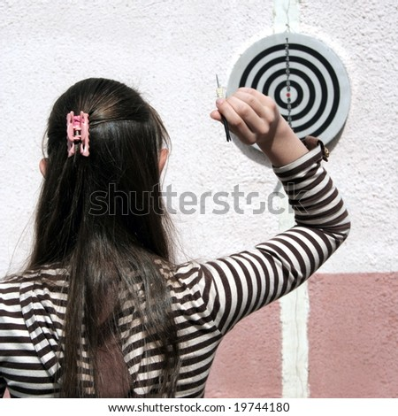 Girl throws dart to target - stock photo