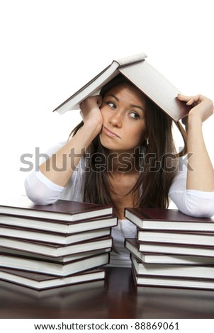 Girl tired of reading books studying school or college bored with the book on head, getting ready for college classes on a white background - stock photo
