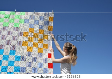 Girl touching a bright patchwork counterpane hanging to dry on a clothes-line. - stock photo