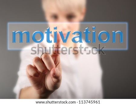 Girl touching screen with motivation button - business concept - stock photo