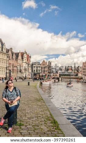 Girl tourist (in focus) on the background of ancient architecture the waterfront of the Leie river in the historic city center with channel and embankment (Graslei and Korenlei), Ghent (Gent) Belgium