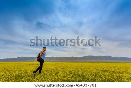 Girl tourist in yellow field - stock photo