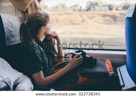 Girl tourist is looking out the window. fast train - stock photo