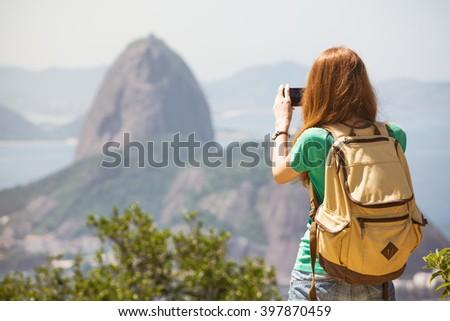 girl tourist taking a photo on a smartphone Pao de Acucar. Rio de Janeiro. - stock photo