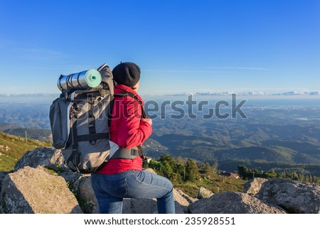 Girl tourist with a backpack on a mountain top. In a campaign in Portugal. - stock photo