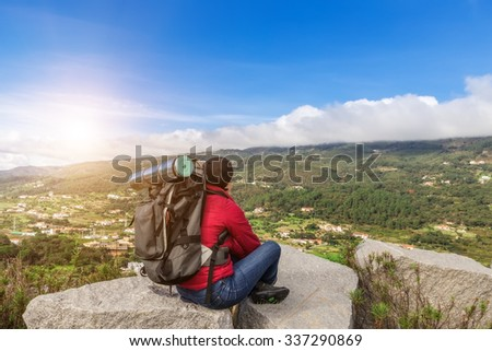 Girl tourist with a backpack resting in a campaign. With views of the Monchique.