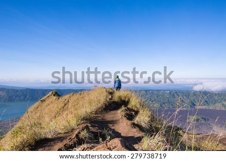 Girl tourist with a backpack walking on top of the Gunung Batur volcano