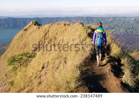 Girl tourist with a backpack walking on top of the Rinjani volcano - stock photo