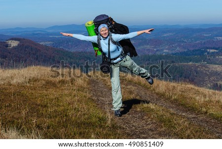 Girl tourist with big backpack in the Carpathian Mountains in autumn