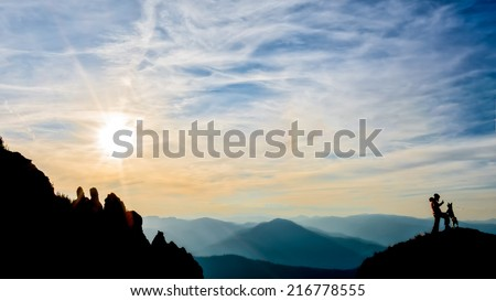 girl training her dog on top of the mountain - stock photo