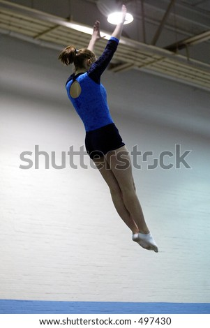 girl trampolining in a blue and black leotard with her arms raised above her head
