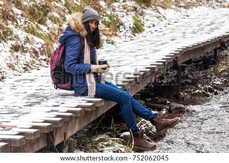 Girl traveler drinking tea in nature in the forest in winter