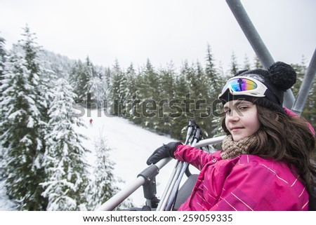 Girl travels a chair lift over ski slope - stock photo