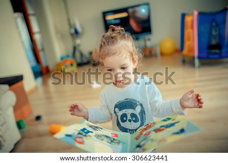 girl trying to read a children's book - stock photo
