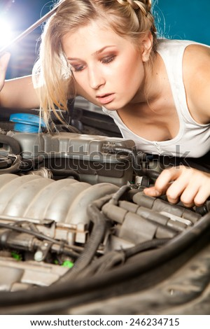 Girl trying to repair their own broken car working on the transmission. - stock photo