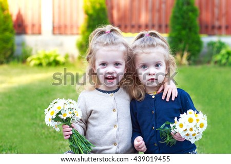 girl twins smiling and holding a bouquet of daisies - stock photo