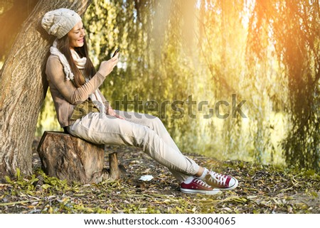 Girl typing message on smart phone in park on autumn day.  - stock photo