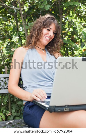 Girl Typing on a Bench in the Park