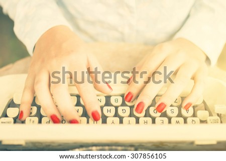 Girl typing on a typewriter, vintage photo effect - stock photo