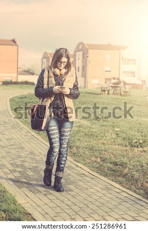 Girl Typing on Smart Phone while Walking at Park. The Girl is Looking at Smart Phone. The Park is in a Residential Area, there are some Houses on Background. - stock photo
