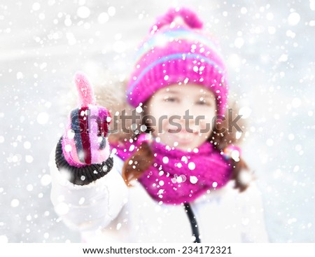 Girl under snow showing her thumb up - stock photo