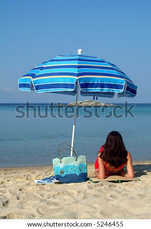 Girl under sunshade on the beach - stock photo