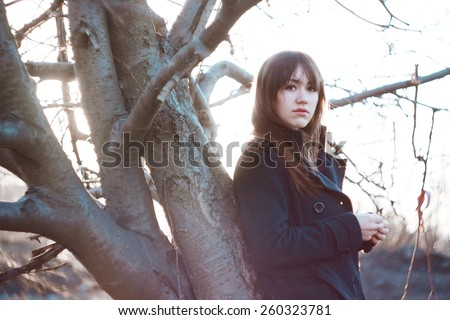 Girl under tree. Emotional portrait of beautiful brunette. Cold spring colors