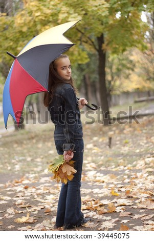 Girl under umbrella and yellow leaves at autumn - stock photo