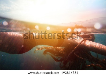 Girl underwater with sun rays. vintage retro style with soft focus, bokeh and sun flare - stock photo