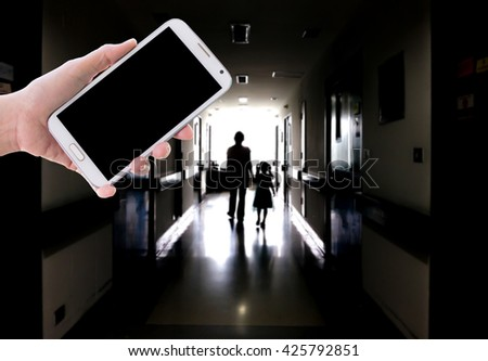 Girl use mobile phone, blur image of a mother and daughter walking on the dark corridor in the hospital. - stock photo